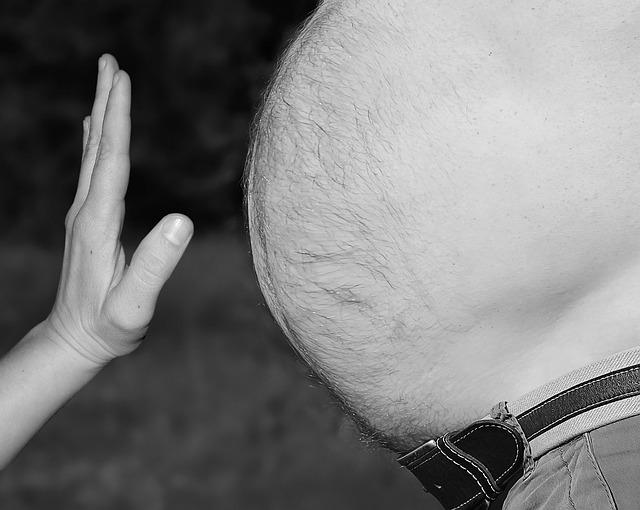 Ruka, která signalizuje, stop rostoucímu mužskému bříšku